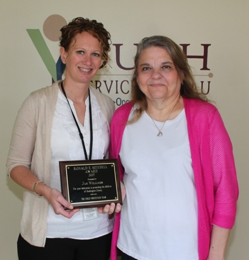 Jan Williams (right), executive director of the Youth Services Bureau of Huntington County, accepts the Ronald Mitchell Award from Alexys Vosmeier, local office director of the Huntington County Department of Child Services Thursday, April 13, at the YSB office.