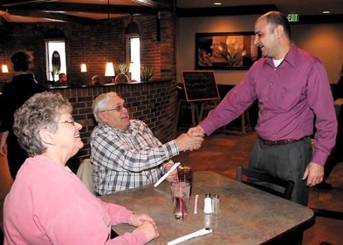 Moe El-Hussein (right), owner of Moe's Restaurant, greets patron Phil Bitzer (center) and his wife Bertha at the restaurant in Huntington.
