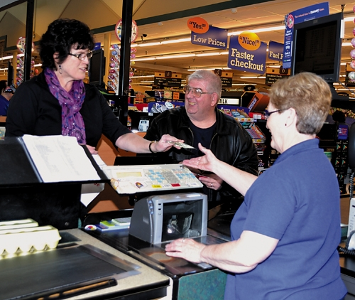 Shopper Tim Konz (center) smiles as Glenda Giggy, woman's leader for Huntington County Farm Bureau Inc., hands Owen's North cashier Pam Wall cash to help pay Konz's grocery bill. Konz was one of several shoppers chosen at random to receive cash.