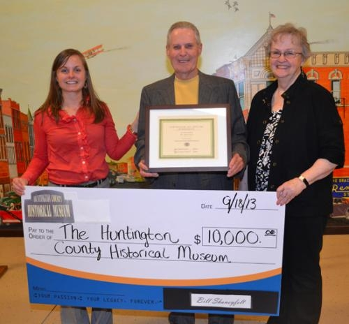 """Sarah Schmidt (left), director of the Huntington County Historical Museum, and Patti Souers (right), president of the Huntington County Historical Society, accept a gift from William """"Bill"""" Shaneyfelt (center) on Wednesday, Sept. 18."""