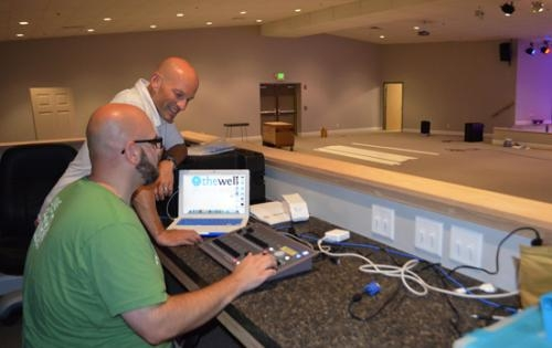 Josh Kesler (background), senior pastor at The Well, checks out the lighting board with Marvin McNew Jr., worship and communication pastor. The church will hold its first service in its new location on Sunday, Aug. 11.
