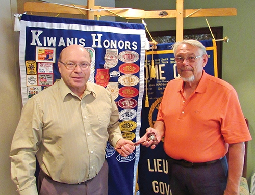 Huntington Metro Kiwanis' newly-installed president, Terry Oden (left), accepts the gavel from Dan Rumple, outgoing president.