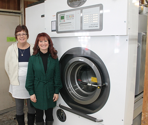 Northside Cleaners Manager Mary Whitesell (left) and owner Chris Zahm stand next to the new Union HXL 8018-C dry cleaning machine that was recently installed at the laundry. The new unit, made in Italy, is more environmentally-friendly than previous machines.