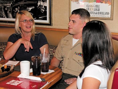 Corporal Nick Middaugh (center) socializes with his mother, Brenda Middaugh (left), and girlfriend Megan Hunsberger on Thursday, Sept. 27, at Applebee's, in Huntington, after walking in and surprising family and friends by returning home.