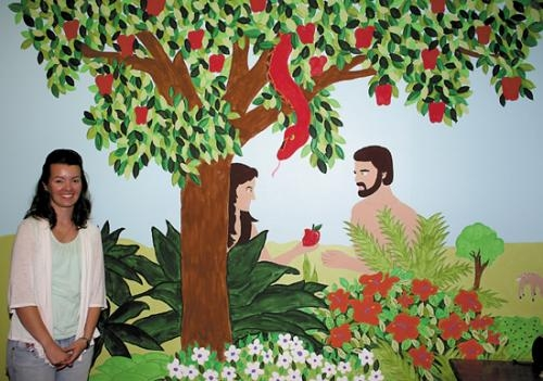 "Kirsten Lautzenhiser, Northview Church of Christ member, stands next to a mural of Adam and Eve that she helped paint in one of the church's four children's worship centers. This room has been named ""Eve's Garden"" and is used for the church's nursery."