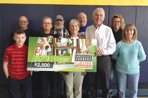 Celebrating a $2,500 grant from America's Farmers Grow Communities program to the Open Door soup kitchen in Huntington are (front row from left) Andrew Lopshire, Sue Christman, Deb Osterholt, Jerry Osterholt and Cindy Johnson; and (back row from left) Tony Little, John Buhler, Mike Bracht and Annette Little.