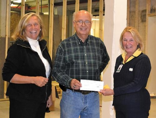 Darlene Garrett (right), chief operating officer of Parkview Huntington Hospital, presents a $25,000 donation to Perry Collins (center), a member of the Roanoke Public Library Building Corporation to fund the Parkview Huntington Program Room.