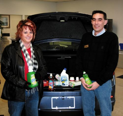 Joe Burgess (right), of Pace Chevrolet, presents donations of personal hygiene, baby care and household cleaning products to Beth Stevens, family self sufficiency coordinator for Pathfinder Services.