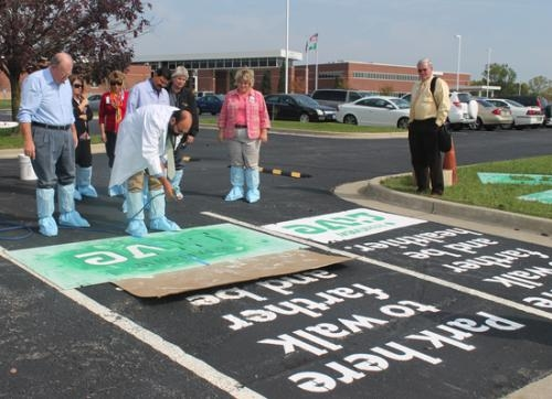 "Ed Strubel (left), pharmacy manager at Parkview Huntington Hospital, paints a remote parking space at Parkview Huntington Hospital on Thursday, Sept. 27, for the hospital's ""Park Farther"" initiative."
