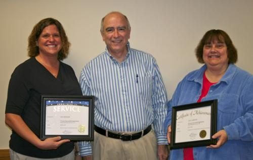 Pathfinder Services President John Niederman (center) presents service awards to Lisa Mettler (left) and Lucy Gibson during an employee recognition program on Monday, Oct. 22.