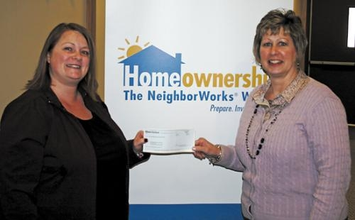 Paula Whiting (right) assistant vice-president for Lake City Bank in Huntington, presents a check for $450 to Natalie Fisher, home buyer education coordinator for Pathfinder Community Connections, at the Pathfinder North Campus in Huntington.