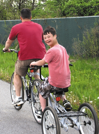 This photo of Roanoke resident Reid Pickard, riding a bicycle with his father Randy Pickard, will be part of a video shown Sept. 22 in Times Square by the National Down Syndrome Society.