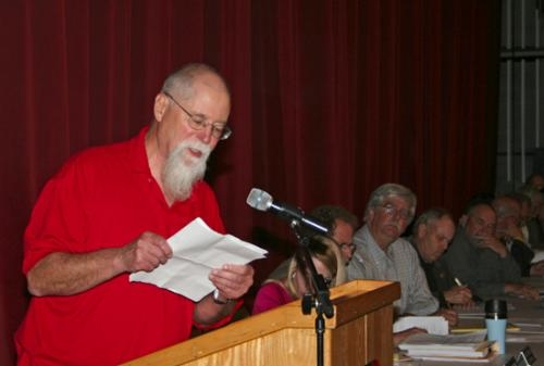 As members of the Huntington County Plan Commission look on, Archie Lintz, a member of Huntington County Concerned Citizens, reads his comments from the podium during the Plan Commission's workshop on the wind farm ordinance, held Wednesday, May 14.