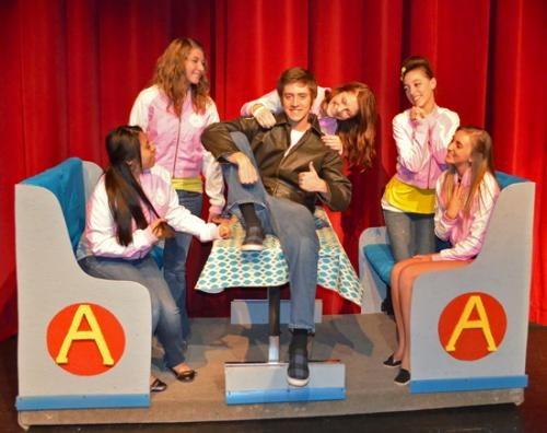 "Female cast members (from left) Alondra Martinez, Madi Waldfogel, Lina Willard, Madie Mettler and Elizabeth Leach shower their affection on ""The Fonz,"" played by Jordan Hersey, on Wednesday, April 17, during play practice at Huntington North High School."