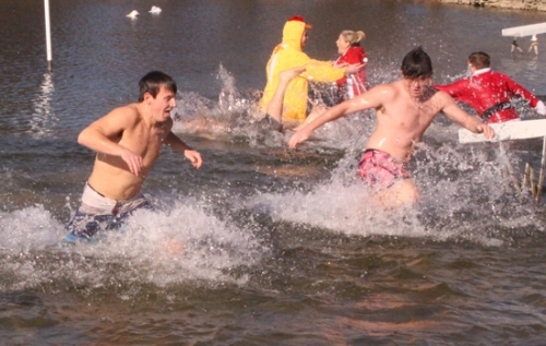Conner McCabe (left), Walker Leas (right) and other participants in the Christmas in Our Town Polar Plunge react to the chilly water in the Markle Pool during the event on Saturday, Dec. 2. The event was a fund-raiser, with all proceeds going to families in need in the community.
