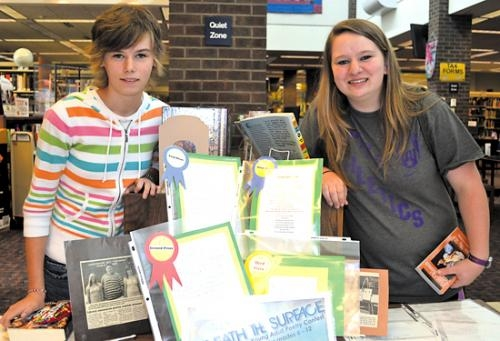 Hailey Stepler (left) and Melissa Westfall pose next to the display at the Huntington City-Township Public Library that includes their winning entries in the library's annual poetry contest.