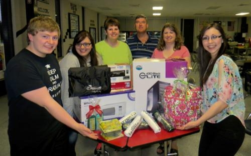 Some of the prizes that will be given away during the Huntington North High School post-prom party are displayed by several HNHS seniors  and  parent steering committee members  recently.