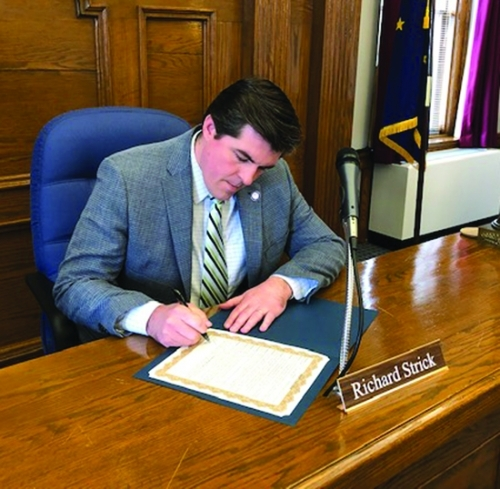 Huntington Mayor Richard Strick signs a proclamation naming the week of March 15 through March 21 as National Safe Place Week. The week raises national awareness about the program, which partners with businesses and volunteers to help youth in crisis situations.