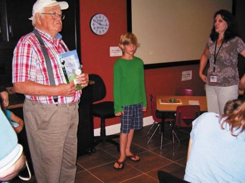 Roanoke Lions Club member Jim Coppick (left) holds the book to be awarded to Simon Fairchild (center) as Karen Baker, library assistant, looks on during the summer reading club party at the Roanoke Public Library.