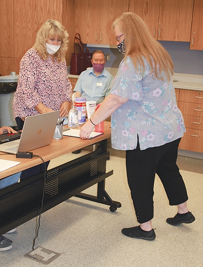 Yvette Runkle, voter registration deputy (left), shows Karen Carpenter, Huntington City-Township Public Library's patron's services clerk (right), how to fill out a voter registration form during a voter registration event on Thursday, Sept. 24 at the library, while the library's assistant director, Eric Fry looks on.