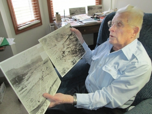 "Bill Jones, a resident of Heritage Pointe of Huntington, looks at copies of some of the aerial photos he took of Hiroshima showing the destruction of the city by the atomic bomb dropped by the United States during World War II. Jones' story is included in a new book by Bluffton author Kayleen Reusser, ""They Did It for Honor: Stories of American WWII Veterans."""