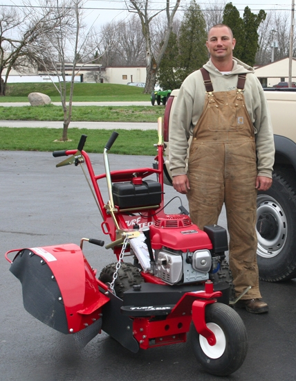 Aaron Reust, owner of Reust Lawn Care, stands with his new Turf Tec Edger, which allows him to offer flower and garden bed redefining and creating to his customers.