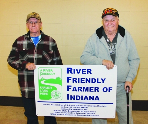 James Minton (left) and his brother, Gary Minton, hold the River Friendly Farmer of Indiana sign that they will post on their farm. They received the Huntington County Soil and Water Conservation District's River Friendly Farmer Award at the SWCD's annual banquet held Tuesday, Feb. 26, at First Merchants Bank Heritage Hall on the Huntington County Fairgrounds.