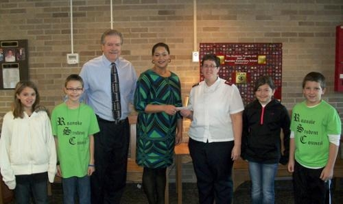 Tinisha Weigelt, Roanoke Kiwanis president (fourth from left), presents a check for $399.21 to Capt. Barbara McCauley, pastor of The Salvation Army, in Huntington, at Roanoke Elementary School recently.