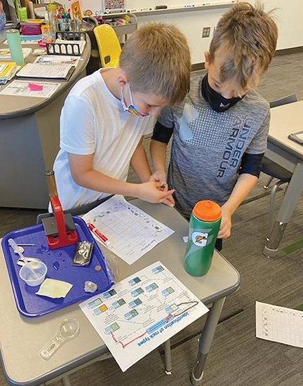 Roanoke Elementary students Bentlee Stine (left) and Maddox Baker participate in a rock detective lab, making a hypothesis on which type of rock each specimen might be.
