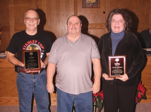 John Stoeckley (left) and JoAnne Kirchner (right) hold plaques presented to them by Dave Tucker, president of the Roanoke Town Council, on behalf of the town in thanks for their years of service to the community. Stoeckley was a member of the town council for 27 years while Kirchner served at the town's clerk-treasurer for 23 years.