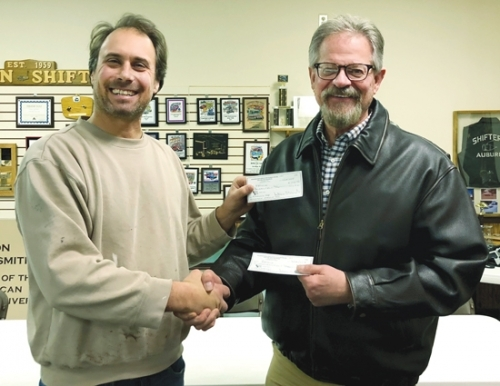 Rolling Into Roanoke Show Director Rick Fisher (left) presents a donation recently amounting to $2,000 to Dave Yarde, executive director of the National Automotive & Truck Museum.