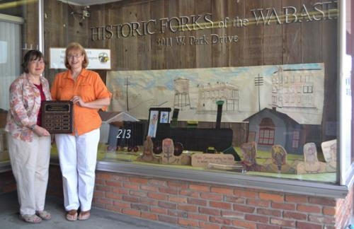 Susan Taylor (left) and P.J. Eddie, of the Historic Forks of the Wabash, stand next to the winning window they decorated for the Heritage Days Window Display contest.