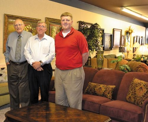 Three generations of Smiths — Bob Smith, Ed Smith and Jordan Smith (from left) — gather inside their downtown Huntington business, Smith Furniture, which was founded by Bob's father, Everett, in 1943. The store is celebrating the start of its 70th year.