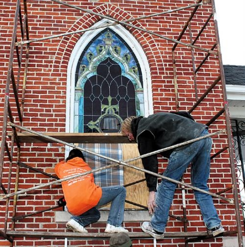 Kealy Skinner (left), owner of Country Panes Stained Glass, reinstalls a stained glass window at Bethel United Methodist Church, in Huntington, on Thursday, Nov. 15, with Rod Schilling.