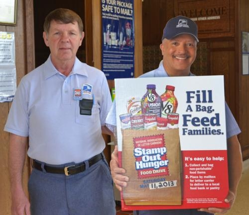 Real-life letter carrier Jack Abbott stands next to a cardboard counterpart at the Huntington Post Office advertising the Stamp Out Hunger food drive to be held on Saturday, May 11.