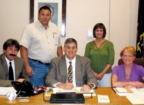 Huntington County Commissioners (seated, from left) Leon Hurlburt, Tom Wall and Kathy Branham sign a proclamation designating April 29-May 6 as Soil and Water Stewardship Week.