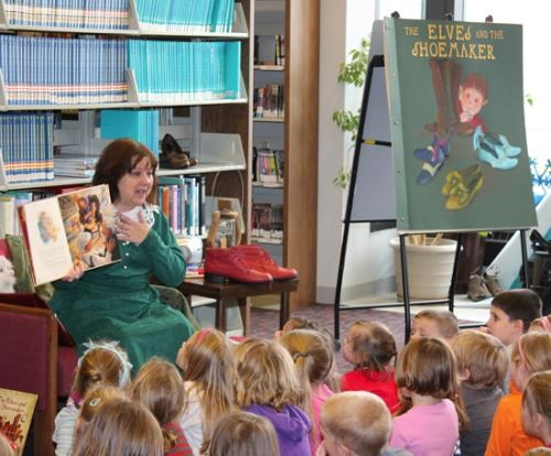 "Kay Stine, director of the children's department at the Huntington City-Township Public Library, reads ""The Elves and the Shoemaker"" to students from Flint Springs Elementary at the library on Thursday, Dec. 6."