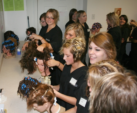 Huntington Beauty College recently opened its doors to Huntington North High School vocational students. Students can participate in either the cosmetology or manicurist programs. Here, students are working on perfecting techniques on their mannequins.