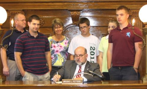 "Huntington Mayor Brooks Fetters (front) signs a proclamation on Wednesday, Sept. 11, recognizing Sept. 15 to Sept. 21 as ""Suicide Prevention Week."""