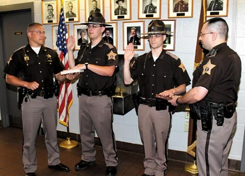 Kurtis Jeffers and Adam Carroll (second and third from left) are sworn in by Chief Deputy Chris Newton (first from left) and K-9 officer Dave McVoy as reserve deputies with the Huntington County Sheriff's Department on Monday, May 6, at the county jail.