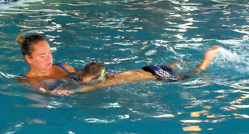 Sara Okuly, swimming instructor, assists a student during a swim class hosted by the Huntington Parks and Recreation Department.