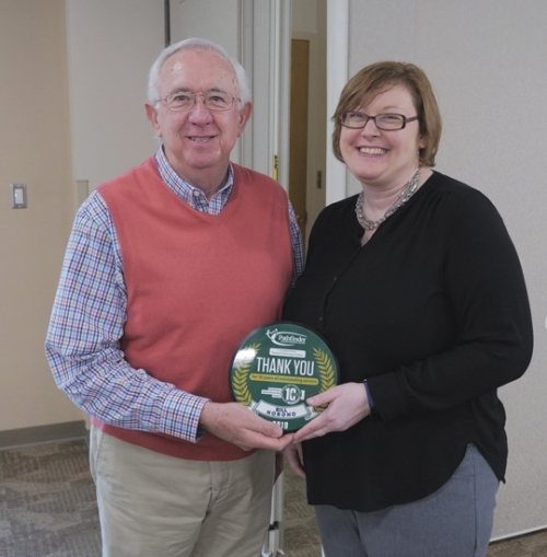 Bill Horoho (left), a 10-year volunteer of the Voluntary Income Tax Assistance program, holds the award he received at a recent dinner to honor volunteers. He is congratulated by Kristy Wall, HomeOwnership counselor and VITA coordinator.