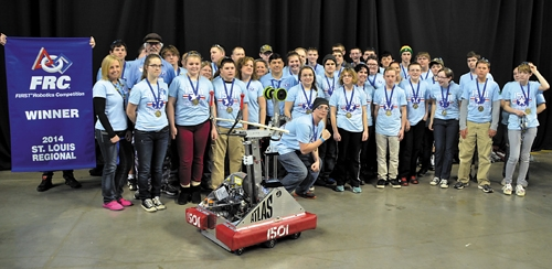 Members of Team THRUST crowd around their robot and first-place banner after winning the robotics regional in St. Louis, MO, on March 15.