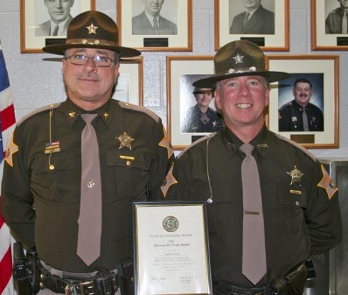 Huntington County Sheriff Terry Stoffel (left) congratulates Deputy Matt Weicht, who holds the Herman Freed Award for best mental attitude presented to him by Gov. Mike Pence during his graduation from the Indiana Law Enforcement Academy on Nov. 1.
