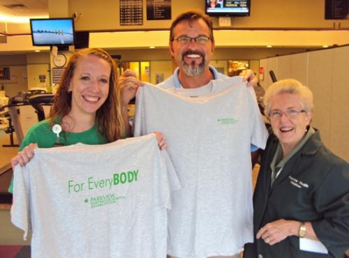 Phyllis Pieper (right), treasurer of the Parkview Huntington Hospital Guild, holds a new therapy T-shirt up to physical therapist Mike Sands, (middle) while physical therapist Kim Case displays the other side of the shirt.