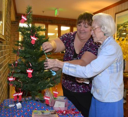 Rhonda O'Reilly, left, coordinator of the Karing for Kids program, and Alma Woodward, a resident of Markle Health & Rehabilitation, place paper angels on a tree at Markle Health on Tuesday, Nov. 6.