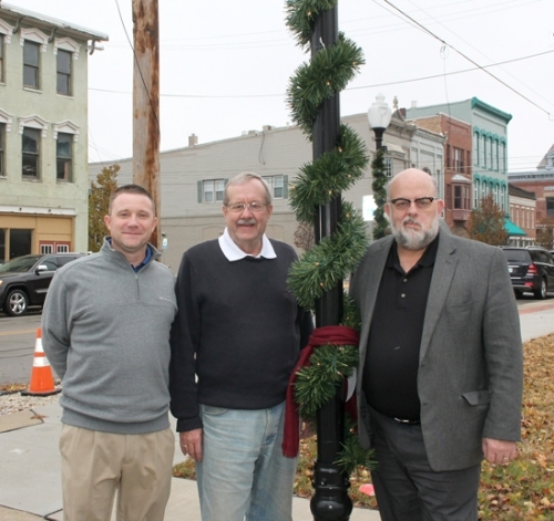 Standing beside a lamppost on Cherry Street decorated for the Christmas season are (from left) Steve Yoder, superintendent of Huntington Parks and Recreation for the City of Huntington; former Huntington Mayor Steve Updike; and current Mayor Brooks Fetters. They have launched a campaign to raise funds to pay for additional decorations for the downtown area.