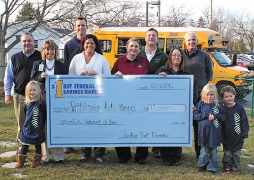 Local business representatives present a check for $17,000 to Pathfinder Kids Kampus, in Huntington, on Friday, Dec. 14, for proceeds raised during the child care center's eighth annual Turkey Trot fund-raiser on Nov. 22.