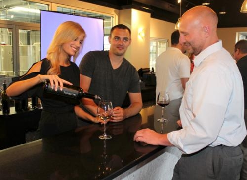 Emily Hart (left) and Eric Harris (center), the owners of Two-EE's Winery, in Roanoke, pour a glass of wine for Nathan Moore during a Roanoke Chamber of Commerce event held at the winery on Thursday, June 20. Two-EE's is now open for business.