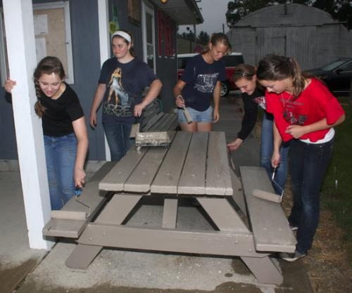 Members of the Huntington North High School Varsity Singers (from left) Erika Kennedy, Emma Davidson, Ashley Okuly, Sophie Smekens and Eileen Mettler paint a picnic table at Huntington's Police Athletic League (PAL) on Thursday, Aug. 8.